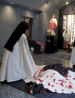 The youngest Sister sprinkles rose petals on the newly professed who is lying prostrate on the cross of flowers.