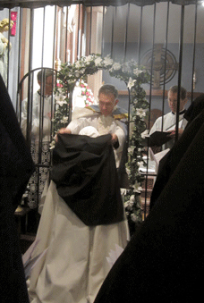 The Priest places the veil on the newly professed