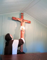 Hanging the new crucifix in the hermitage