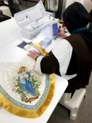 Sister sews on the gold fringe on to the edge of the cope hood